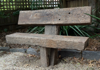 A solid red gum timber garden seat anchored into the ground